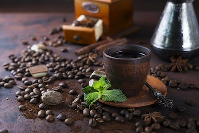Coffee in cup and mint leaves on dark stone table.