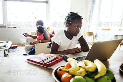 Black girl using laptop at home