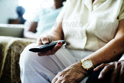 Senior people sitting on a couch holding TV remote control