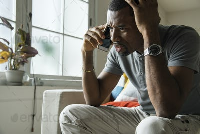 Black guy talking phone with angry emotion