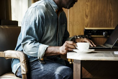 Man working on laptop and having a hot drink