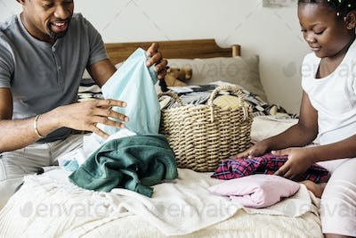 Dad and daughter folding clothes in bedroom together