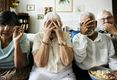 Senior friends sitting on the couch with horrified reaction