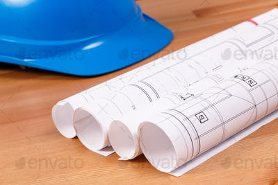 Rolls of electrical blueprints for engineer jobs and protective blue helmet, technology concept