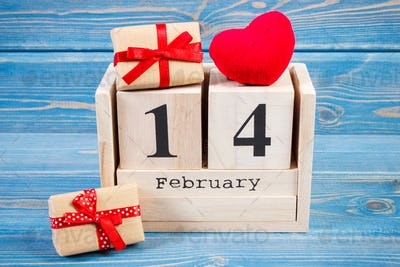 Date 14 February on cube calendar, wrapped gifts and red heart, Valentines day decoration