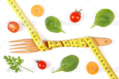 Wooden fork wrapped centimeter and fresh vegetables, concept of slimming and healthy nutrition