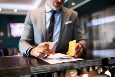 Mature businessman at hotel reception.