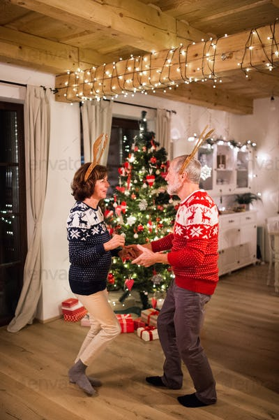 Senior couple dancing by Christmas tree in the evening.