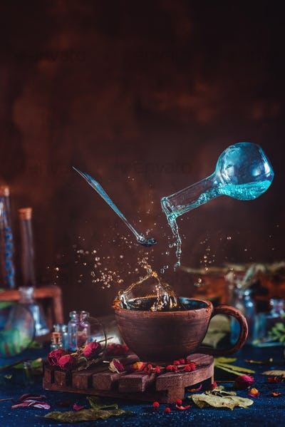Flying potion bottle with pouring liquid in a magical still life. Brewing magical tea.