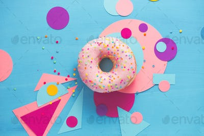 Pink glazed donut on a colorful background with geometric shapes. Color block food photography.