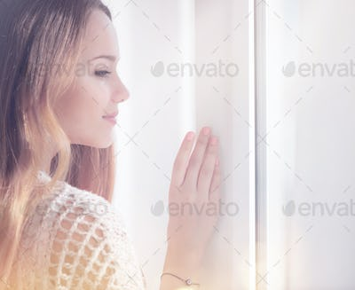 Young beauty romantic woman looking out the window