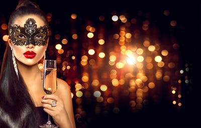 Sexy model woman with glass of champagne wearing venetian masque