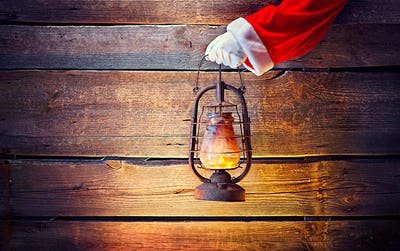 Christmas scene. Santa's hand holding vintage oil lamp over wood