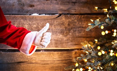Santa Claus thumb up gesture over Christmas holiday wooden backg