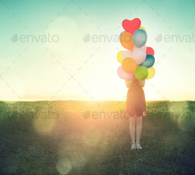 Beauty teenage girl on summer field with colorful air balloons o