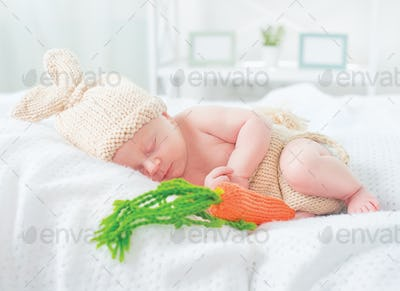 Cute two weeks old smiling newborn baby boy wearing knitted bunn