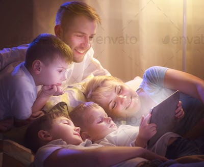Happy family together watching movie on tablet computer in dark