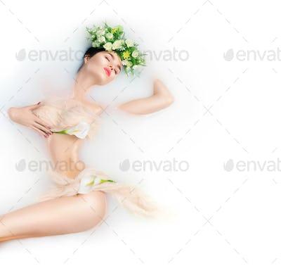 Beautiful fashion model girl taking milk bath, spa and skincare