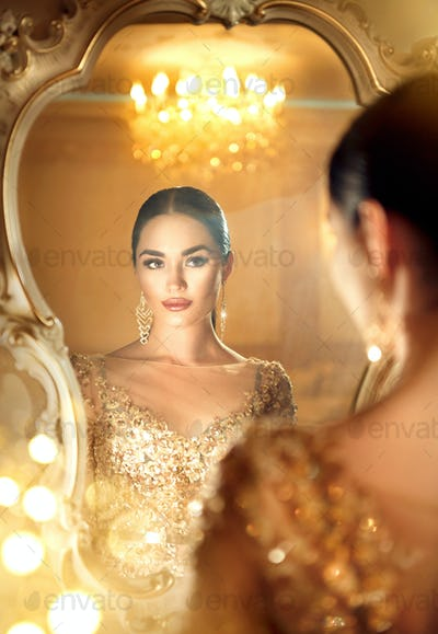 Beauty glamour lady looking in the mirror. Gorgeous woman in bea