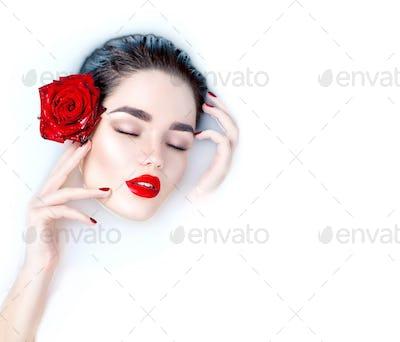 Beautiful fashion model girl taking milk bath, spa and skin care