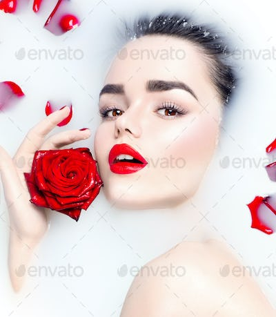 Beauty young model girl with bright makeup and red rose flower r