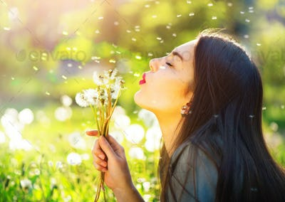 Beautiful young woman blowing dandelions and smiling