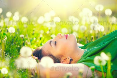 Beautiful young woman lying on the field in green grass and dand