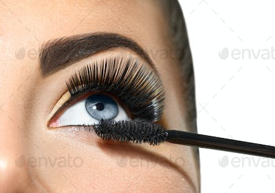Long lashes closeup. Beautiful woman applying mascara on her eye