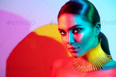 Fashion model woman in colorful bright lights posing. Portrait o