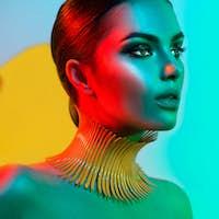 Fashion model woman in colorful bright lights posing. Portrait o
