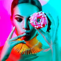 Fashion model woman posing in studio with donut in colorful brig