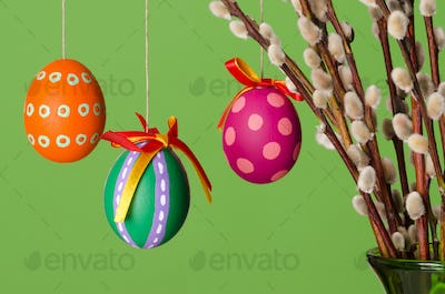 Paschal eggs on willow bouquet, horizontal over green