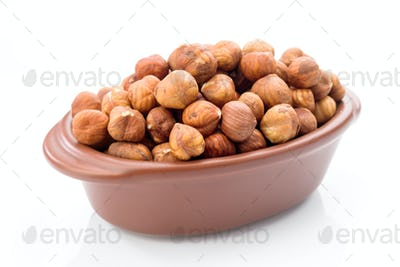 hazelnuts in clay bowl on white background