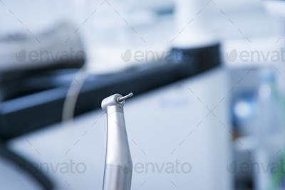 Dentist instruments.  Dental diamond cylinder bur with hand-piece. Blurred dental office background