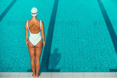 Rear view of female swimmer on poolside
