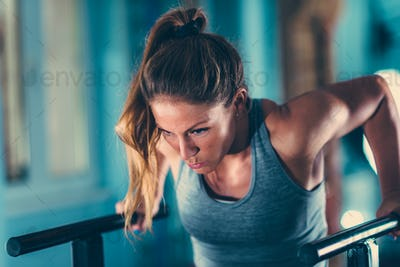 Female athlete in a gym, parallel bars exercising