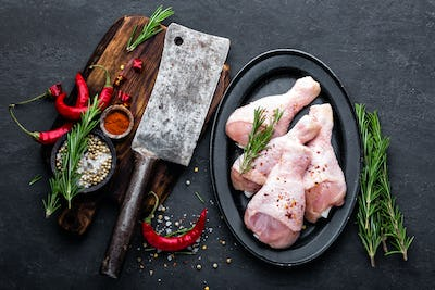 Chicken legs, drumsticks and ingredients for cooking, raw meat on black background, top view