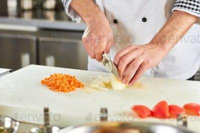 Chef chopping juicy yellow onion.