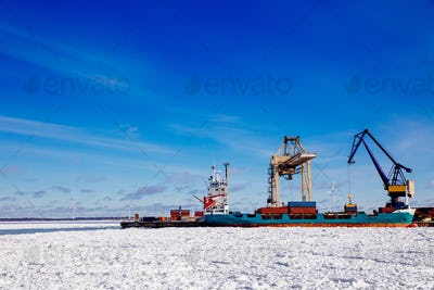 Industrial port with containers in winter, vessel loading in port of Finland