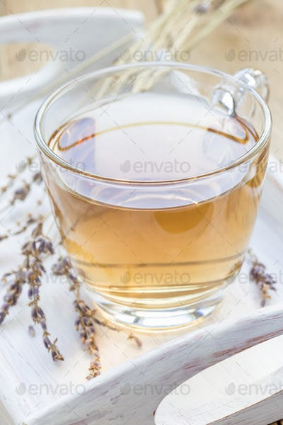 Healthy herbal lavender tea in glass cup with lavender flowers on background, vertical