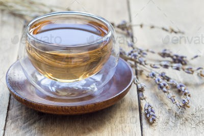 Healthy herbal lavender tea in oriental glass cup with flowers on background, horizontal