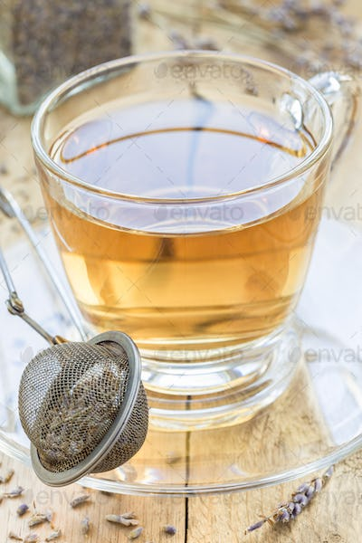 Healthy herbal lavender tea in a glass cup with lavender flowers on background, vertical