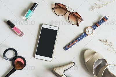 woman cosmetics and fashion items with cellphone and copy space