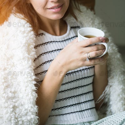 Young beautiful girl with a cup of coffee sitting on the couch at home.
