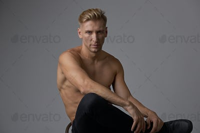Attractive young man posing with naked torso sitting on a chair