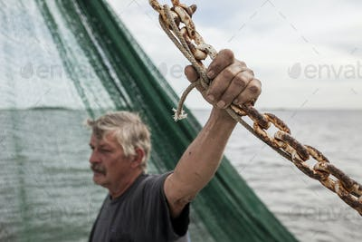 Commercial fisherman holding rusty chain