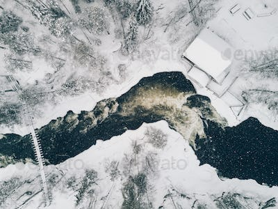 Aerial view of Icy river flowing through a beautiful snowy winter scenery in Finland.