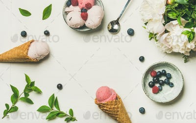 Ice cream scoops, peonies and berries over white background