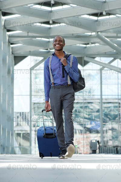 african american business man walking at airport with luggage