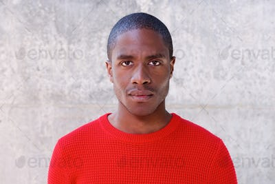 Young african american man in red sweater staring